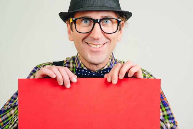 Uśmiechnięty frajerem trzymający czerwoną afisz. papierowa karta z pustą przestrzenią. zabawny nerd w kapeluszu retro i okularach. szczęśliwy człowiek z pustym plakatem.