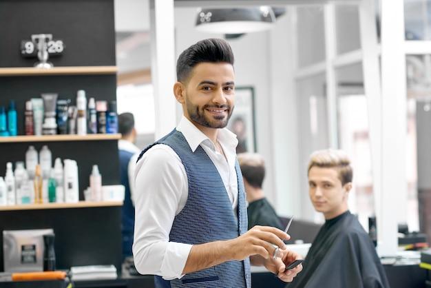 Uśmiechnięty fryzjer męski stoi blisko młodego klienta siedzi blisko lustra.