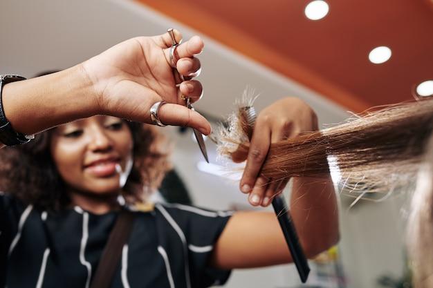 Uśmiechnięty fryzjer tnący rozdwojone końcówki