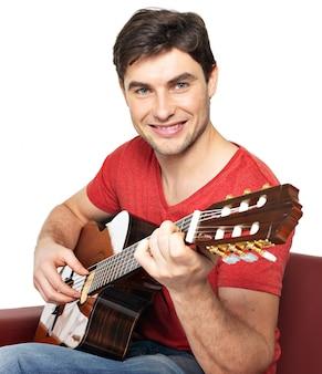 Uśmiechnięty gitarzysta gra na gitarze akustycznej izolować na białym tle. przystojny, młody mężczyzna siedzi z gitarą na kanapie