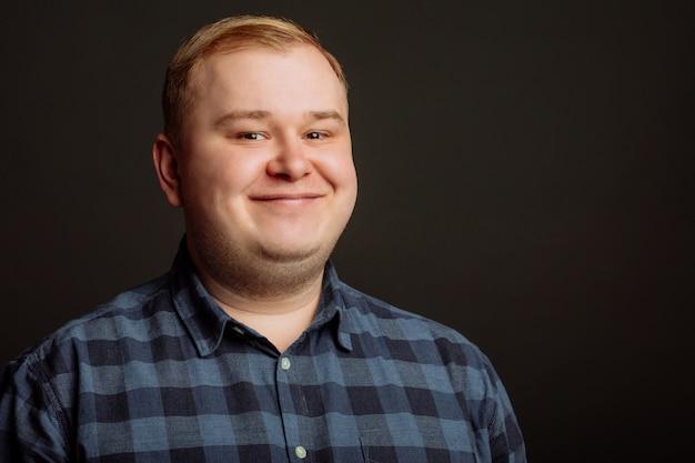 Uśmiechnięty gruby mężczyzna na czerni ścianie