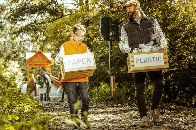Uśmiechnięty herbaciarz i uczeń niosący pudła posortowanej śmieci po ścieżce w lesie w dobry dzień