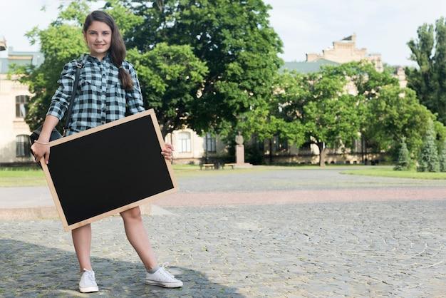 Uśmiechnięty highschool dziewczyny mienia blackboard