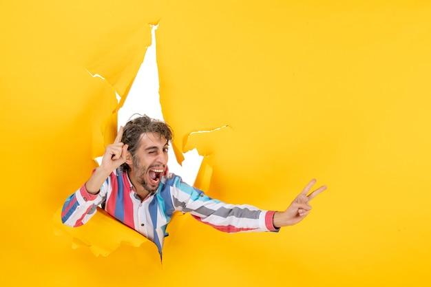 Uśmiechnięty i emocjonalny młody człowiek pozuje w podartym żółtym papierowym tle dziury, wskazując w górę i wykonując gest zwycięstwa