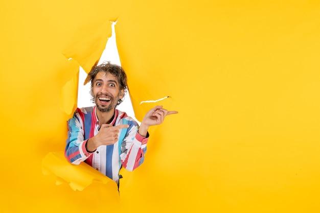 Uśmiechnięty i emocjonalny młody człowiek pozuje w podartym żółtym tle dziury w papierze i wskazuje coś
