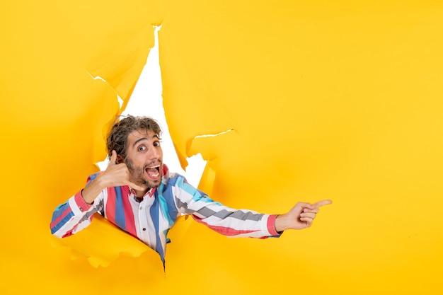 """Uśmiechnięty i emocjonalny młody człowiek pozuje w podartym żółtym tle dziury w papierze, wskazując coś i wykonując gest """"zadzwoń do mnie"""