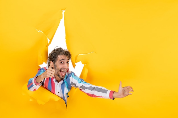 Uśmiechnięty i emocjonalny młody człowiek pozuje w podartym żółtym tle dziury w papierze, wykonując ok gest