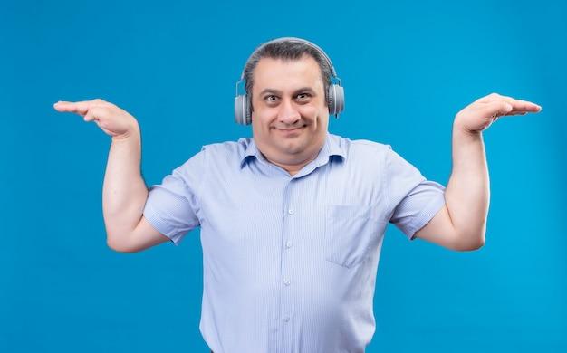 Uśmiechnięty i pozytywny człowiek w niebieskiej koszuli, ubrany w słuchawki, udając, że leci trzymając ręce w górę na niebieskim tle