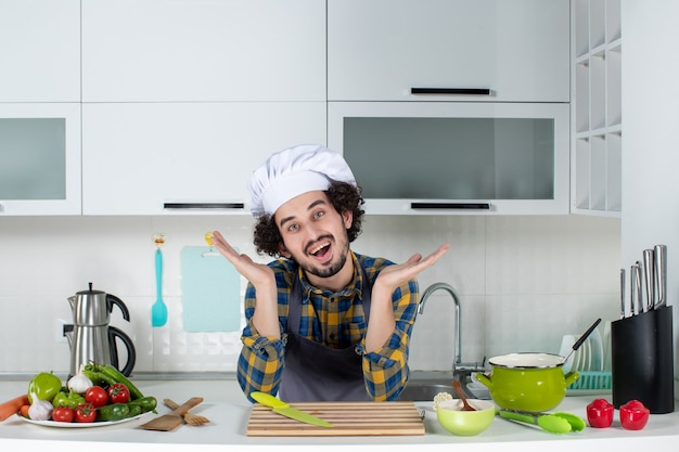 Uśmiechnięty i pozytywny męski szef kuchni ze świeżymi warzywami pozuje w białej kuchni