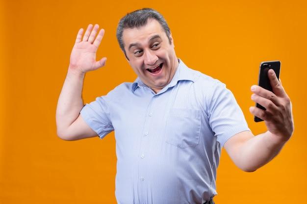 Uśmiechnięty i pozytywny mężczyzna w średnim wieku w niebieskich pasiastych słuchawkach z koszuli, machający ręką, przywitający się podczas rozmowy wideo przy użyciu smartfona, stojąc na pomarańczowym tle