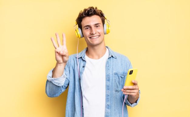 Uśmiechnięty i przyjazny, pokazując numer trzy lub trzeci z ręką do przodu, odliczając. koncepcja słuchawek i smartfona