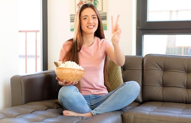 Uśmiechnięty i przyjazny, pokazujący cyfrę dwa lub sekundę z ręką do przodu, odliczanie