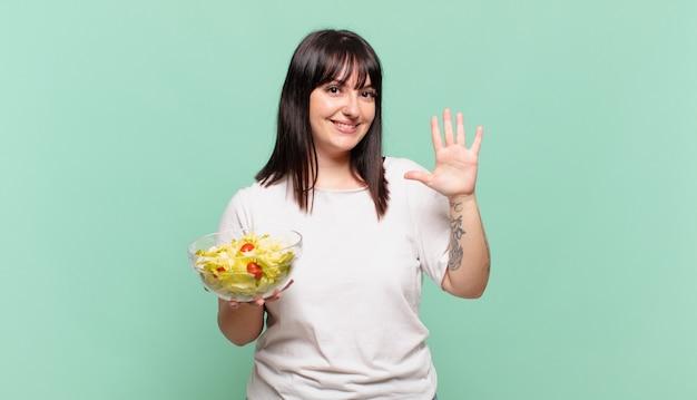 Uśmiechnięty i przyjazny, pokazujący numer pięć lub piąty z ręką do przodu, odliczanie