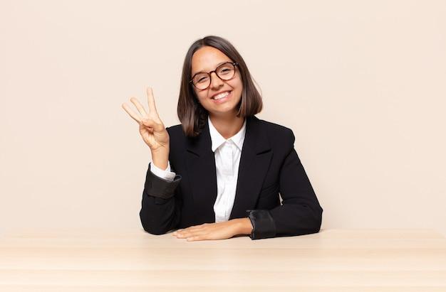 Uśmiechnięty i przyjazny, pokazujący numer trzy lub trzeci z ręką do przodu, odliczanie