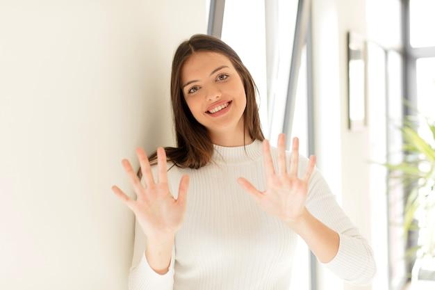 Uśmiechnięty i przyjazny wyglądający na cyfrę dziesięć lub dziesiątą z odliczającą ręką do przodu