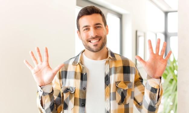 Uśmiechnięty i przyjazny wyglądający, pokazujący numer dziesięć lub dziesiątą z ręką do przodu, odliczający