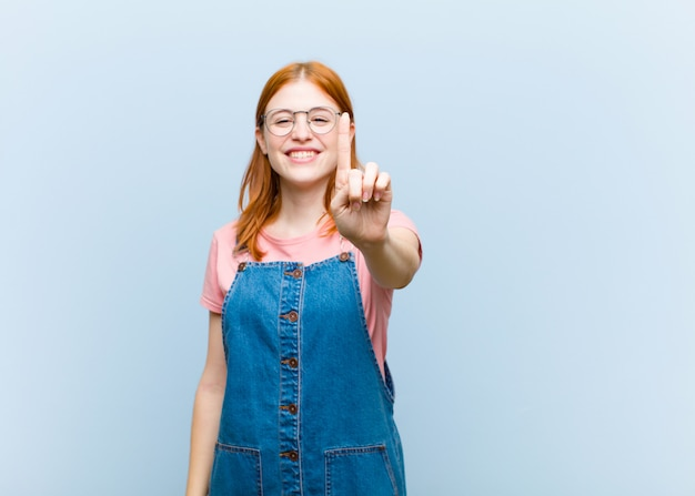 Uśmiechnięty i przyjazny wyglądający, pokazujący numer jeden lub pierwszy z ręką do przodu, odliczający