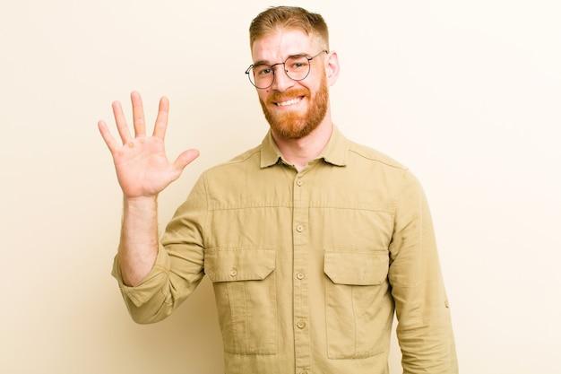 Uśmiechnięty i przyjazny wyglądający, pokazujący numer pięć lub piąty z ręką do przodu, odliczający
