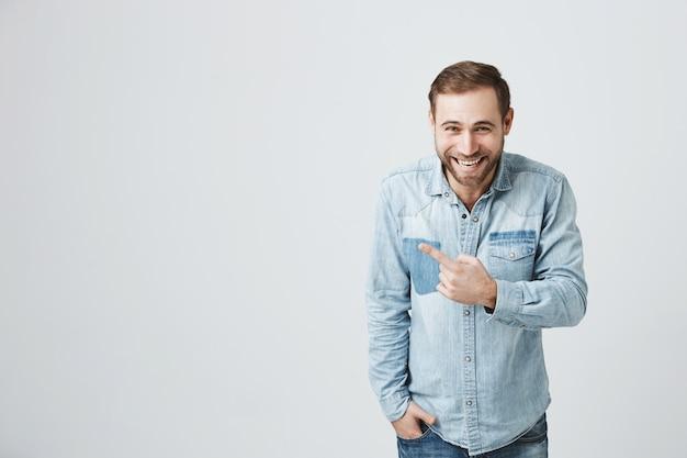 Uśmiechnięty i roześmiany szczęśliwy facet wskazujący palec w lewo