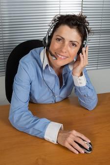 Uśmiechnięty i szczęśliwy bizneswoman w centrum telefonicznego biurze