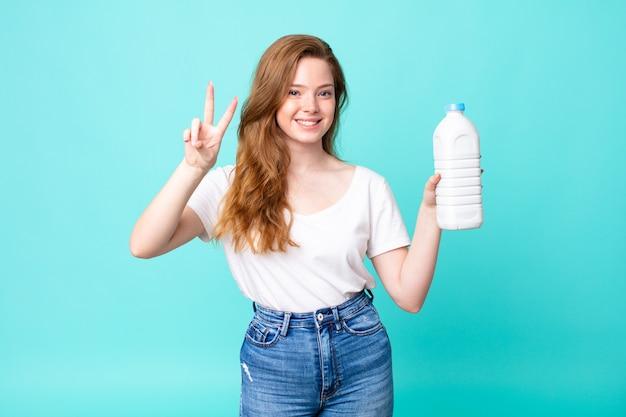 Uśmiechnięty i szczęśliwy, gestykulujący zwycięstwo lub pokój i trzymający butelkę mleka