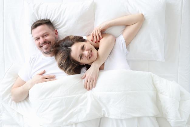 Uśmiechnięty i szczęśliwy mężczyzna i kobieta leży w łóżku obejmując