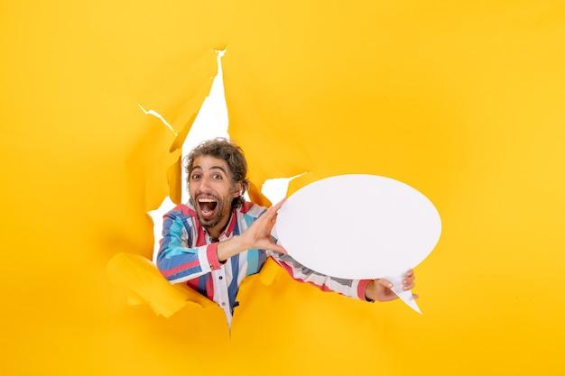 Uśmiechnięty i szczęśliwy młody facet wskazujący białą stronę z wolną przestrzenią w rozdartej dziurze w żółtym papierze