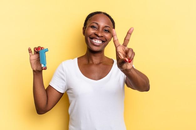 Uśmiechnięty i wyglądający na szczęśliwego, beztroskiego i pozytywnego, gestem zwycięstwa lub pokoju jedną ręką. koncepcja astmy