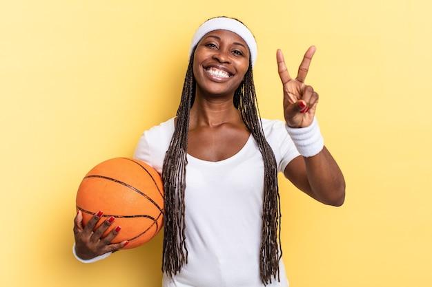 Uśmiechnięty i wyglądający na szczęśliwego, beztroskiego i pozytywnego, gestem zwycięstwa lub pokoju jedną ręką. koncepcja koszyka