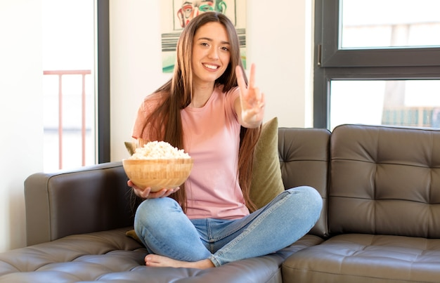 Uśmiechnięty i wyglądający na szczęśliwy, beztroski i pozytywny, gestem zwycięstwa lub pokoju jedną ręką
