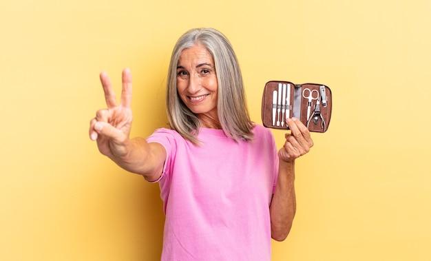 Uśmiechnięty i wyglądający przyjaźnie, pokazując numer dwa lub drugi z ręką do przodu, odliczając trzymając walizkę z narzędziami do paznokci