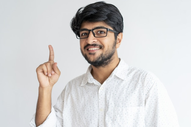 Uśmiechnięty indyjski facet wskazuje upwards i patrzeje kamerę