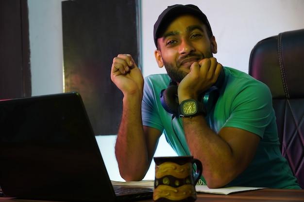 Uśmiechnięty indyjski facet z laptopem pracującym lub uczącym się online