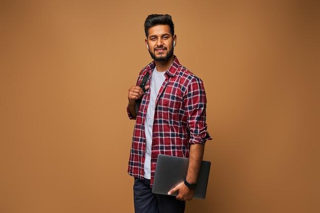 Uśmiechnięty indyjski mężczyzna w swobodnym zamknięciu z laptopem i plecakiem na pastelowej ścianie