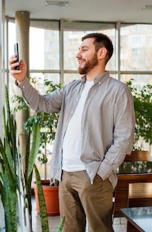 Uśmiechnięty inteligentny człowiek ma rozmowę telefoniczną przez połączenia wideo w nowoczesnym biurze miejskim lub kawiarni.
