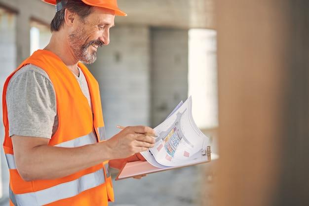 Uśmiechnięty inżynier budowlany przeglądający plany domów w dłoniach