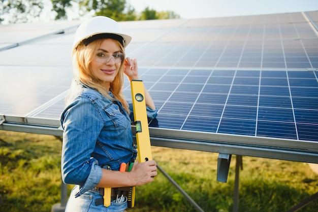 Uśmiechnięty inżynier i panel słoneczny za nią