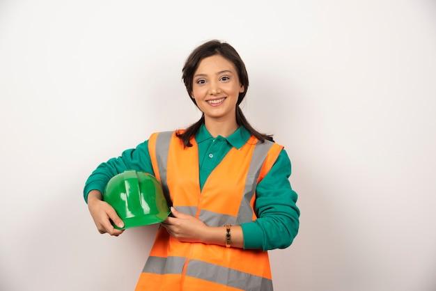 Uśmiechnięty inżynier kobieta trzyma hełm na białym tle.