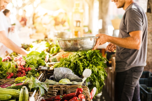 Uśmiechnięty jarzynowy sprzedawca sprzedaje organicznie warzywa przy sklepu spożywczego rynkiem