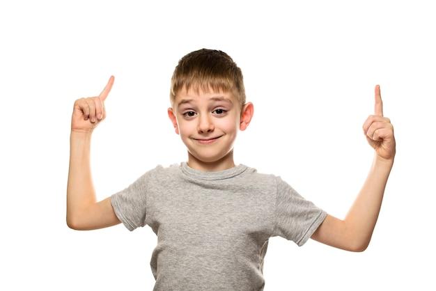 Uśmiechnięty jasnowłosy chłopiec w szarej koszulce wstaje i wskazuje palcami wskazującymi w górę