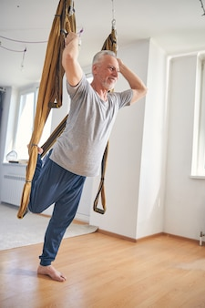 Uśmiechnięty jogin trzymający się środkowych uchwytów jedwabnego hamaka podczas treningu
