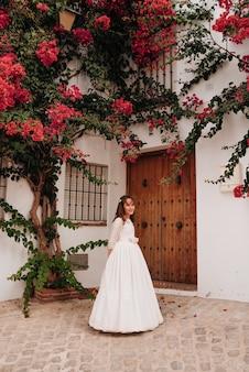 Uśmiechnięty kaukaski dziewczyna ubrana w sukienkę do komunii obok dużego drzewa z różowymi kwiatami