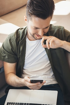 Uśmiechnięty kaukaski mężczyzna rozmawia przez telefon komórkowy i trzyma laptopa na kolanach