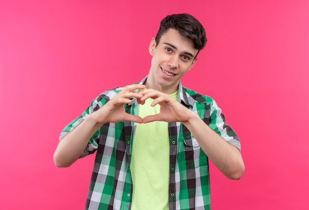 Uśmiechnięty kaukaski młody facet na sobie zieloną koszulę pokazując gest serca na na białym tle różowym tle
