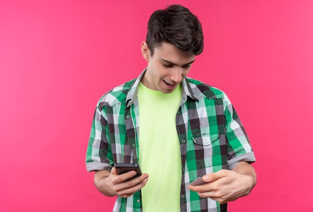 Uśmiechnięty kaukaski młody facet na sobie zieloną koszulę, trzymając telefon i patrząc karty kredytowej na rękę na na białym tle różowym