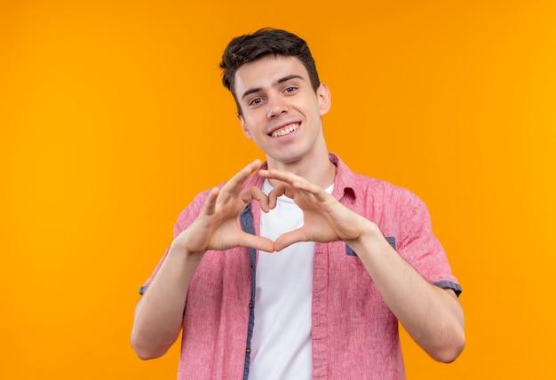 Uśmiechnięty kaukaski młody facet ubrany w różową koszulę pokazując gest serca na na białym tle pomarańczowym tle