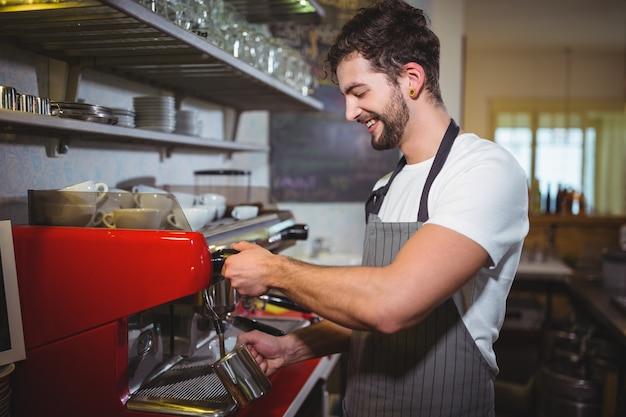 Uśmiechnięty kelner czyni kawę