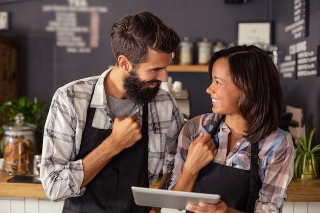 Uśmiechnięty kelner i kelnerka interakcji podczas korzystania z cyfrowego tabletu