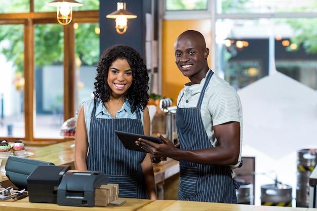 Uśmiechnięty kelner i kelnerka używa cyfrową pastylkę przy kontuarem w kawiarni