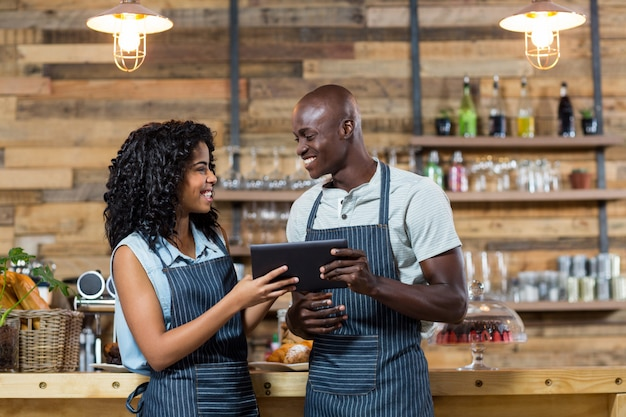 Uśmiechnięty kelner i kelnerka używa cyfrową pastylkę przy kontuarem